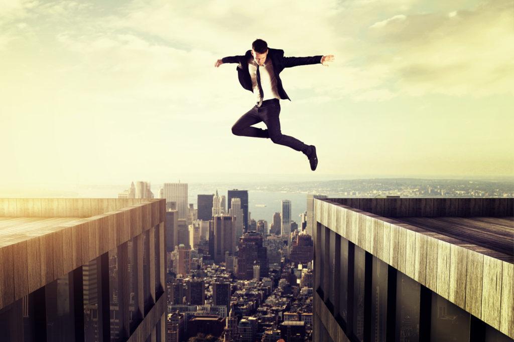 Image d'un homme qui saute entre deux bâtiments