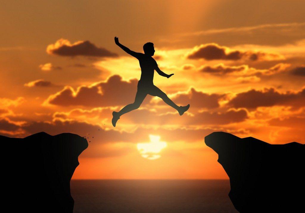Homme qui saute d'une falaise à l'autre